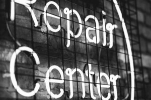 Photo en noir et blan d'un panneau lumineu à néon repair center